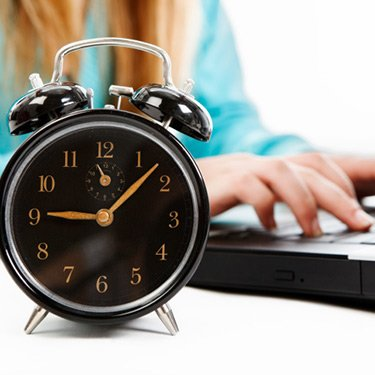 Female-typing-on-laptop-with-clock-showing-time_web