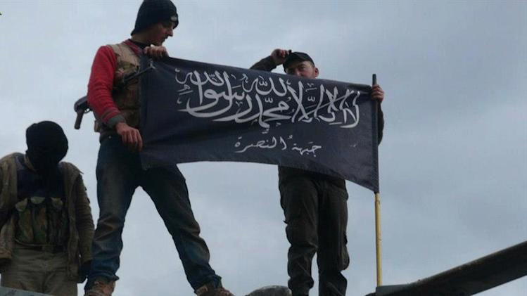 "This citizen journalism image provided by Edlib News Network, ENN, which has been authenticated based on its contents and other AP reporting, shows rebels from al-Qaida affiliated Jabhat al-Nusra, wave their brigade flag as they step on the top of a Syrian air force helicopter, at Taftanaz air base that was captured by the rebels, in Idlib province, northern Syria, Friday Jan. 11, 2013. Islamic militants seeking to topple President Bashar Assad took full control of a strategic northwestern air base Friday in a significant blow to government forces, seizing helicopters, tanks and multiple rocket launchers, activists said. The Arabic words on the flag read:""There is no God only God and Mohamad his prophet, Jabhat al-Nusra (their brigade name)"". (AP Photo/Edlib News Network ENN)"