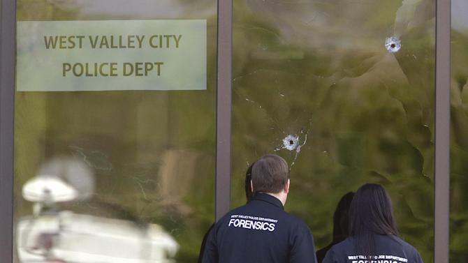 Members of the West Valley City Police Forensics Unit examine bullets holes in a window at the West Valley City Police Department Monday, April 29, 2013, in West Valley City, Utah. Authorities in a Salt Lake City suburb say a man shot after pulling a gun in a police lobby told officers months ago that he wanted to be shot by police. (AP Photo/Rick Bowmer)