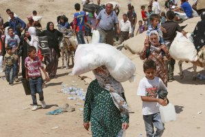 Syrian refugees cross into Iraq at the Peshkhabour…