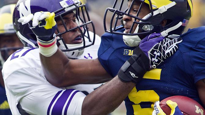 Northwestern safetey Jared Carpenter, left, tries to stop Michigan running back Justice Hayes (5) in the first quarter of an NCAA college football game, Saturday, Nov. 10, 2012, in Ann Arbor, Mich. (AP Photo/Tony Ding)