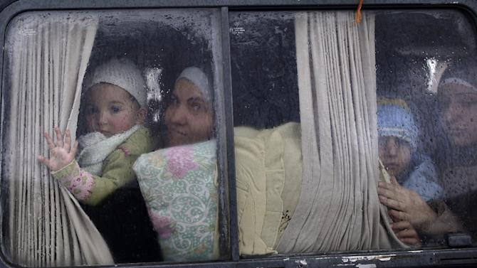 Syrian refugees, who fled their home in Idlib due to a government airstrike, look out of a vehicle's window just after crossing the border from Syria to Turkey, in Cilvegozu, Turkey, Thursday, Dec. 20, 2012. (AP Photo/Muhammed Muheisen)