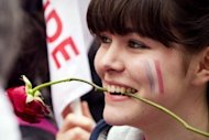 A young supporter with a rose in her mouth waits with other supporters in front of the campaign headquarters of the Socialist Party (PS) in Paris, during the presidential election second round vote