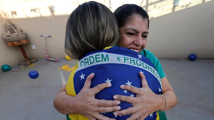 Silvia Santos, facing camera, embraces her daughter Ana Carolina at their home in Brasilia, Brazil, Thursday, June 19, 2014. All the members of the Silva family were born with an extra digit on each hand as a result of a genetic condition known as polydactyly. Rather than recoil in the face of constant stares by curious onlookers the 14 members of the family spanning four generations seem to embrace their physical differences with pride. (AP Photo/Eraldo Peres)