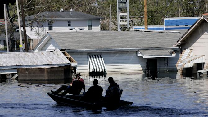 FILE - In this Sept. 7, 2005 file photo, a search and rescue squad uses a small boat in the floodwaters of the Ninth Ward in New Orleans. (AP Photo/Eric Gay, File)