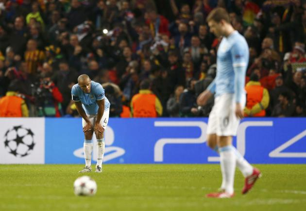 Manchester City's Vincent Kompany and Edin Dzeko react after Barcelona's second goal during their Champions League round of 16 first leg soccer match at the Etihad Stadium in Manchester