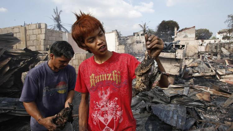 Residents recover burnt chickens from the ruins of houses destroyed by a fire in Malabon, Metro Manila