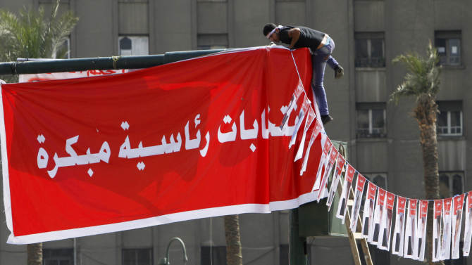 "An Egyptian protester hangs an Arabic banner reading, ""early presidential elections"", during a protest in Tahrir Square, the focal point of Egyptian uprising, in Cairo, Egypt, Friday, May 17, 2013. Hundreds of protesters gathered to demand early presidential elections and the removal of the Muslim Brotherhood's regime. (AP Photo/Amr Nabil)"