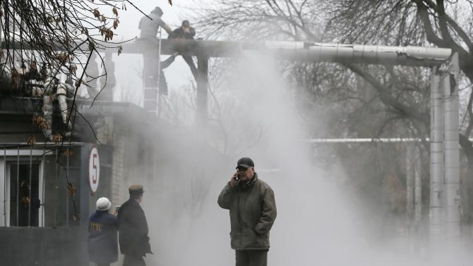 A man talks on a phone as workers repair a heating pipeline at a site hit by shelling in Donetsk, eastern Ukraine