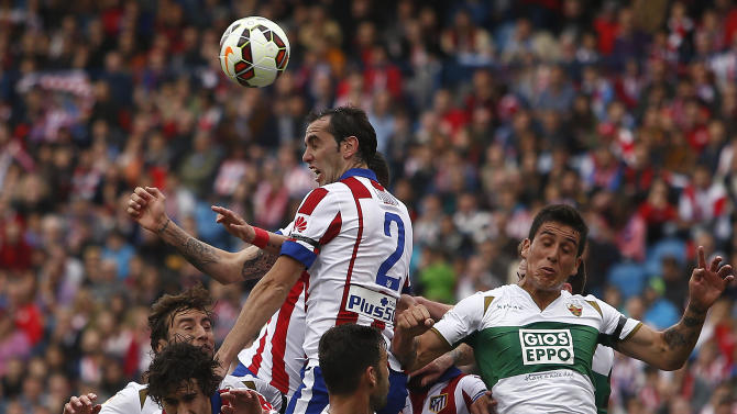 Atletico's Diego Godin, centre top, jumps in between players during a Spanish La Liga soccer match between Atletico Madrid and Elche at the Vicente Calderon stadium in Madrid, Spain, Saturday, April 25, 2015. (AP Photo/Andres Kudacki)