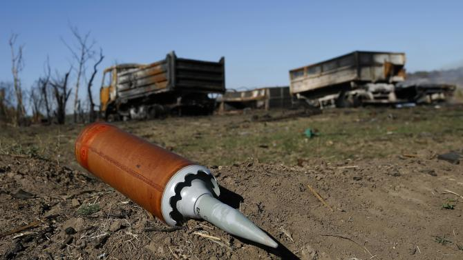 Unexploded shell is seen at the site of recent shelling at the destroyed Ukrainian military camp near the village of Dmytrivka