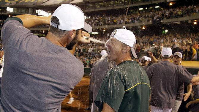 Oakland Athletics' Brandon Inge has champagne shot into his mouth as the team celebrates after clinching a wild card berth in the American League at the end of a baseball game against the Texas Rangers on Monday, Oct. 1, 2012, in Oakland, Calif. (AP Photo/Ben Margot)