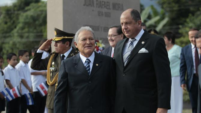 El Salvador President Salvador Sanchez Ceren and his Costa Rican counterpart Guillermo Solis pose for a picture after the inauguration of the Mora y Canas monument in San Salvador
