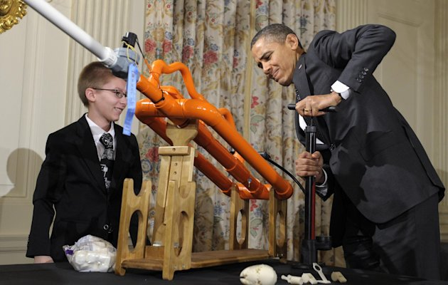 President Barack Obama pumps up a gun designed by Joey Hudy, left, of Phoenix, Ariz., left,  to shoot a marshmallow in the State Dining Room of the White House in Washington, Tuesday, Feb. 7, 2012, du