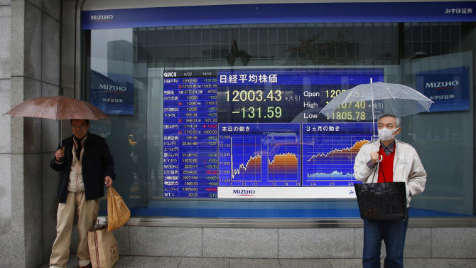 Men wait for a signal to change in front of an electronic stock indicator in Tokyo, Japan, Tuesday, April 2, 2013. A slowdown in U.S. factory production sent Asian stock markets lower Tuesday, while Japan's Nikkei slipped as the yen rose against the dollar. (AP Photo/Shizuo Kambayashi)