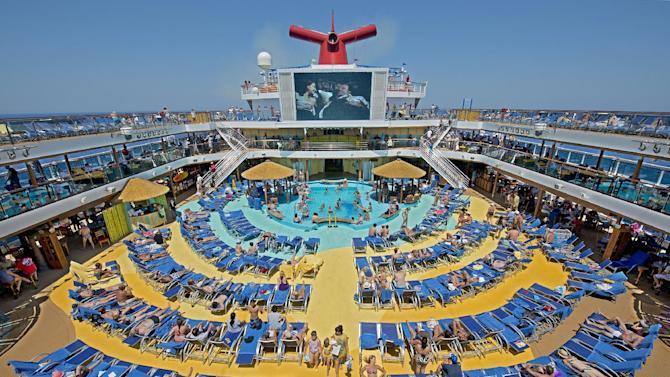 "In this June 23, 2012 photo provided by Carnival Cruise Lines, vacationers aboard the Carnival Breeze enjoy sunbathing at sea while viewing a movie at the Carnival's Seaside Theatre, a lido deck poolside 270-square-foot LED screen offering concerts, sporting events and other programming throughout the day as well as nightly ""Dive In Movies. (AP Photo/Carnival Cruise Lines, Andy Newman)"