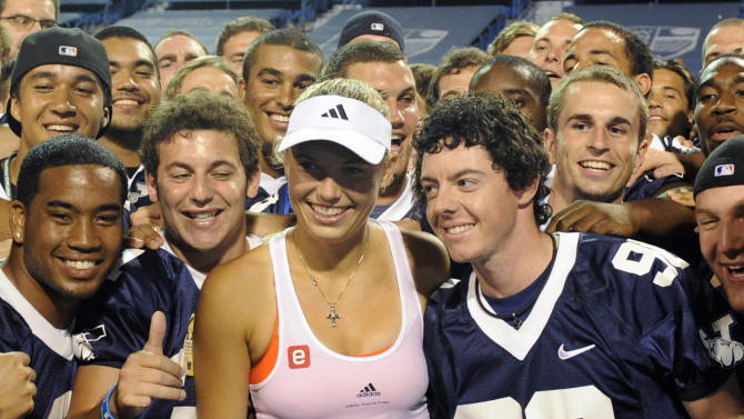 Caroline Wozniacki, of Denmark, celebrates with boyfriend Rory McIlroy and the Yale football team after her 7-6 (2) 6-3 semifinal victory over Francesca Schiavone, of Italy, at the New Haven Open tennis tournament in New Haven, Conn., on Friday, Aug. 26, 2011. (AP Photo/Fred Beckham)