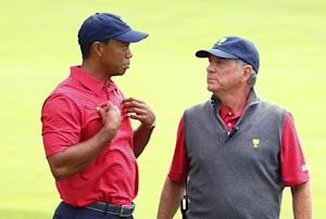 U.S. Team players Woods and Haas confer on the 11th hole during the second practice round for the 2013 Presidents Cup golf tournament at Muirfield Village Golf Club in Dublin, Ohio