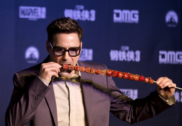 U.S. actor Robert Downey Jr. tries out &quot;bingtanghulu,&quot; a traditional Chinese snack, during a world premiere event of his new movie &quot;Iron Man 3&quot; at a Beijing hotel Saturday, April 6, 2013. (AP Photo/Andy Wong)