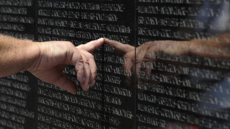 A visitor to the Vietnam Veteran's Memorial touches the name of a fallen soldier etched on the wall of the memorial in Washington, Friday, May 25, 2012. On Monday, the Vietnam Veterans Memorial Wall will begin the national commemoration of the Vietnam Warís 50th anniversary. (AP Photo/Susan Walsh)
