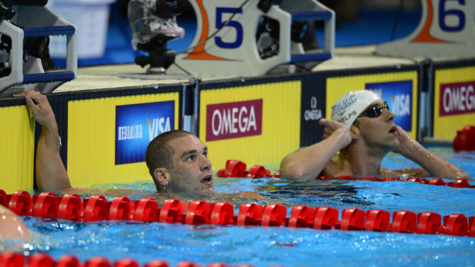 Bobby Bollier, left, and Michael Phelps look at the clock after competing in a men's 200-meter butterfly semifinal at the U.S. Olympic swimming trials, Wednesday, June 27, 2012, in Omaha, Neb. (AP Photo/Mark J. Terrill)