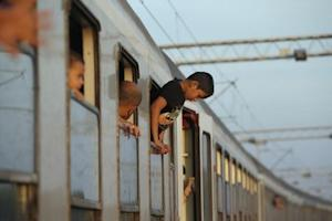 Migrant waits to depart from railway station in Tovarnik