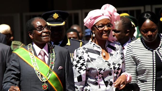 """Zimbabwe President Robert Mugabe, left, and his wife Grace, arrive for celebrations to mark 32 years of independence of Zimbabwe, in Harare, Wednesday, April 18, 2012. In an address Mugabe said that political violence must be """"buried in the past"""" to move the nation toward free and unhindered elections. (AP Photo)"""