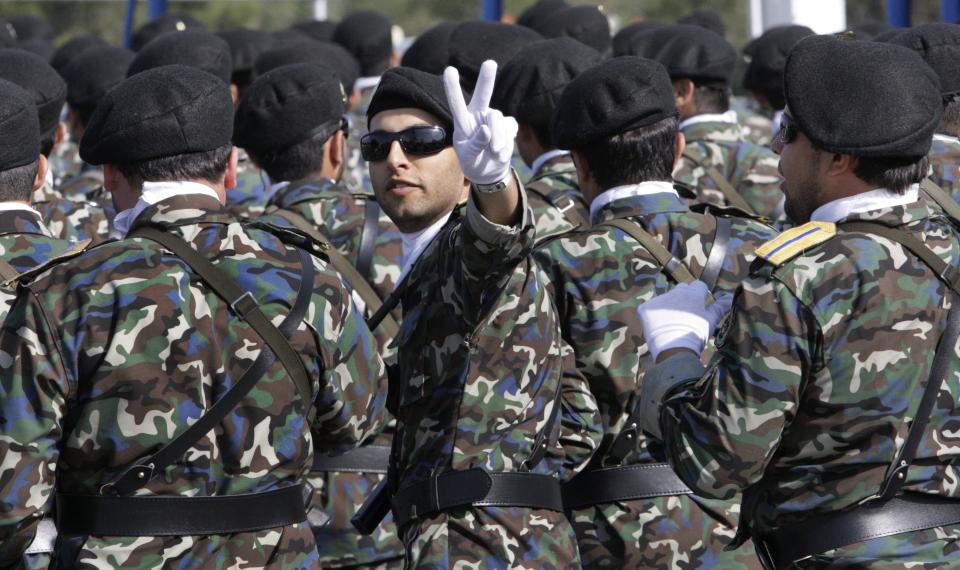 An Iranian soldier flashes the victory sign during a military parade commemorating National Army Day in front of the mausoleum of the late revolutionary founder Ayatollah Khomeini, outside Tehran, Iran, Tuesday, April 17, 2012. (AP Photo/Vahid Salemi)