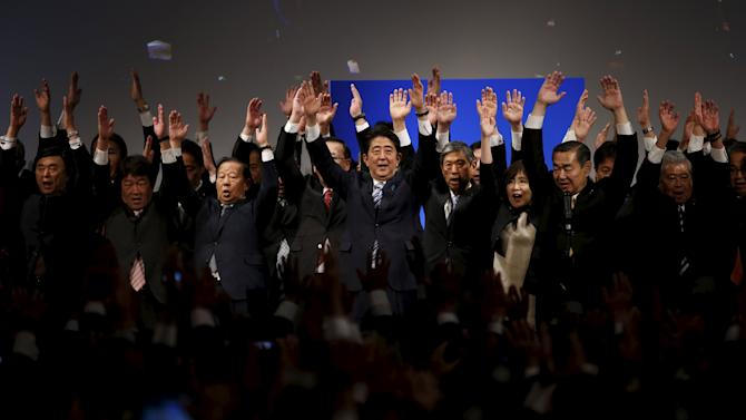 "Japan's PM Abe, who is also the ruling LDP leader, raises his arms as he shouts ""Banzai"" (or ""Cheers"") with his party lawmakers during a ceremony for the LPD's 60th anniversary in Tokyo"
