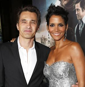 """FILE - This Oct. 24, 2012 file photo shows actors Olivier Martinez, left, and Halle Berry at the Los Angeles premiere of Berry's film, """"Cloud Atlas,"""" in the Hollywood section of Los Angeles. Berry has married Martinez at a weekend ceremony in a church near a chateau in France's Burgundy region. The owner of the Chateau de Vallery, where the couple stayed with their 60 guests, said on Sunday July 14, 2013, that the betrothal a day earlier ended with a dinner and fireworks display. (Photo by Todd Williamson/Invision/AP, File)"""