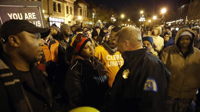 Protester LaTosha Baker confronts St. Louis Police chief Sam Dotson Tuesday, Nov. 25, 2014, in St. Louis, Mo. Missouri's governor ordered hundreds more state militia into Ferguson on Tuesday, after a night of protests and rioting over a grand jury's decision not to indict police officer Darren Wilson in the fatal shooting of Michael Brown, a case that has inflamed racial tensions in the U.S. (AP Photo/Jeff Roberson)