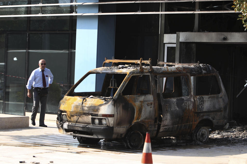 A security guard walks near a destroyed van outside the entrance of Microsoft's offices in northern Athens, Wednesday, June 27, 2012. Assailants attacked the offices of Microsoft early Wednesday, driving a van through the front doors and setting off an incendiary device that burned the building entrance, police said. (AP Photo/Thanassis Stavrakis)