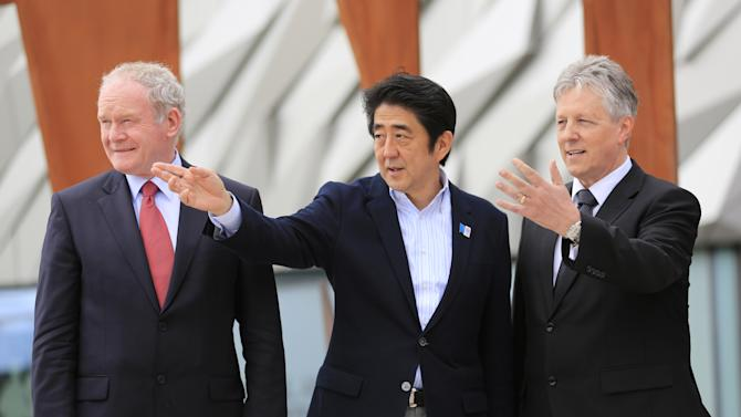 Japan's Prime Minister Shinzo Abe, centre, joins Northern Ireland First Minister Peter Robinson, right, and Northern Ireland Deputy First Minister Martin McGuinness, left, during a visit to the Titanic visitor centre, Belfast, Northern Ireland, Tuesday, June 18, 2013.  The prime minister visited Belfast to discuss trade following the G8 summit.   (AP Photo/Peter Morrison)