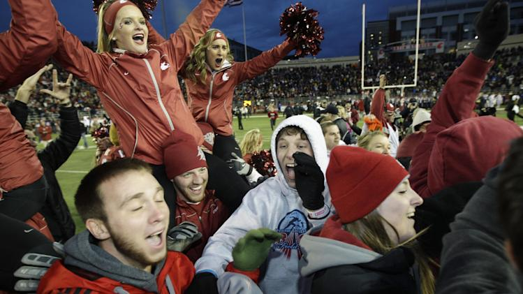 Fans  and cheerleaders celebrate on the field after Washington State defeated Washington 31-28 in overtime at an NCAA college football game on Friday, Nov. 23, 2012, in Pullman, Wash. (AP Photo/Ted S. Warren)