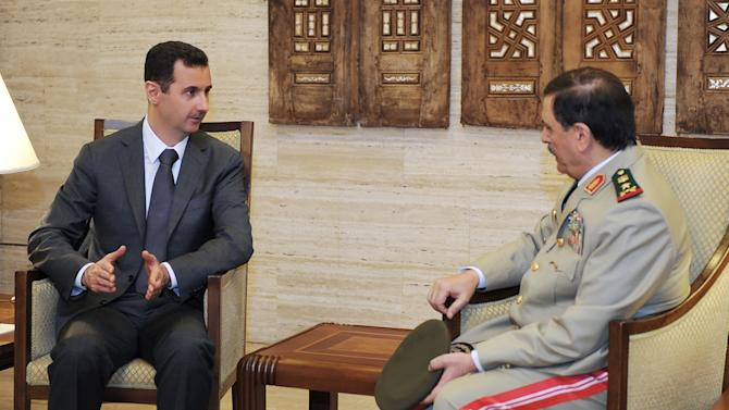 FILE - In this file photo released by the Syrian official news agency SANA on July 19, 2012, Syrian President Bashar Assad, left, meets with Fahd Jassem al-Freij, Syria's new Defense Minister, in Damascus, Syria. Syrian President Bashar Assad's regime received last week the worst blow since the country's crisis began 17 months ago in what many thought would quickly bring the Assad family four-decade dynasty to an end but the government appears to have absorbed the shock of the explosion that killed four top security officials and it's on the offensive again. (AP Photo/SANA, File)
