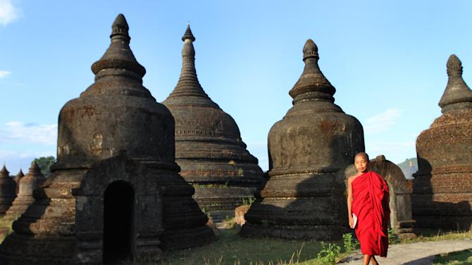 In this photo taken on Nov. 8, 2012, a Buddhist monk walks along ancient pagodas in Mrauk-U, Rakhine state, western Myanmar. Mrauk-U itself has been spared the bloodshed between the Buddhist Rakhine and the Muslim Rohingya that has scarred other parts of Rakhine state. It is calm, and for foreign tourists, safe. But just 10 kilometers (six miles) to the south, there is a village where civilians were reportedly beheaded in a massacre last month that saw women and children slaughtered, then buried in mass graves. Across western Myanmar's Rakhine state, the United Nations is distributing emergency supplies of food and shelter to terrified villagers who have fled burning homes. A nighttime curfew is in force. (AP Photo/Khin Maung Win)