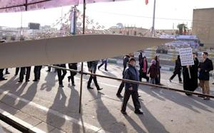 People walk near an Iranian-made missile during a ceremony …