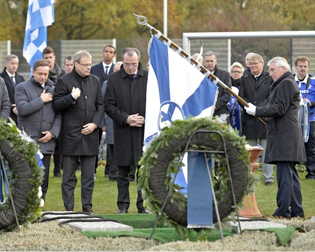 Schalke legend striker Klaus Fischer, supervisory board  chairman  Clemens Toennies, board member Peter Peters and sporting manager Horst Heldt, from right, stand at the grave of Adolf Urban, a storie