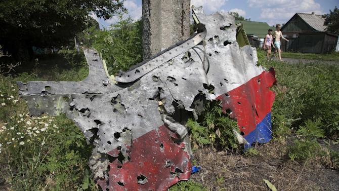 Children walk past a piece of wreckage from the Malaysia Airlines jet downed over Ukraine, in Petropavlivka village, Donetsk region, eastern Ukraine Wednesday, July 23, 2014. TIndependent military analysts said Wednesday that the size, spread, shape and number of shrapnel impacts visible in an AP photograph of a piece of the wreckage all point to a missile system like the SA-11 Buk. (AP Photo/Dmitry Lovetsky)