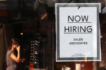 """A """"Now Hiring"""" sign hangs on the door to the Urban Outfitters store at Quincy Market in Boston"""