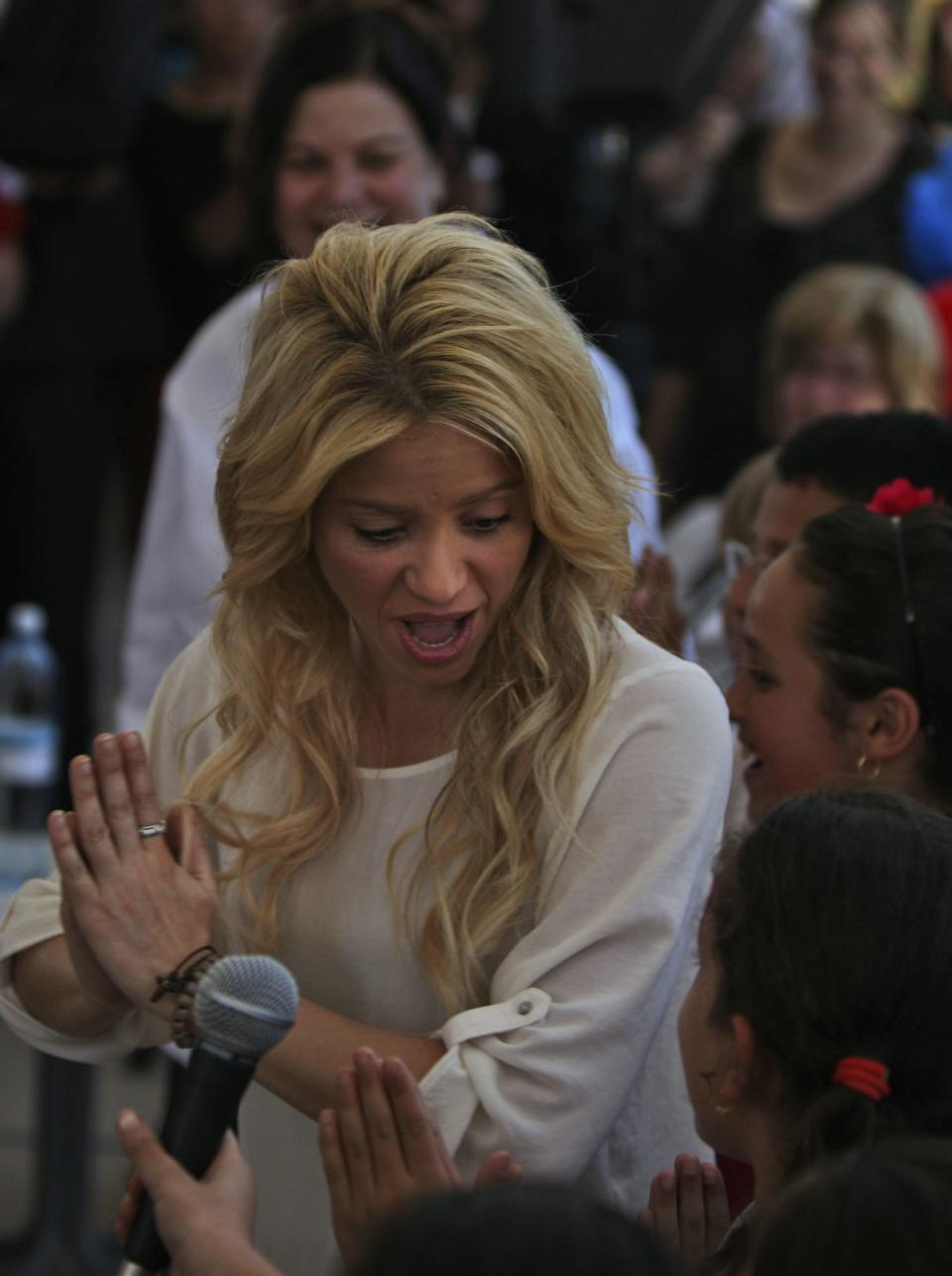 Colombian singer Shakira, left, dances with children while visiting a school in Jerusalem, Tuesday, June 21, 2011. Shakira is attending the Presidential Conference, sponsored by Israeli President Shimon Peres and will take part in panel alongside comedian Sarah Silverman. (AP Photo/Tara Todras-Whitehill)