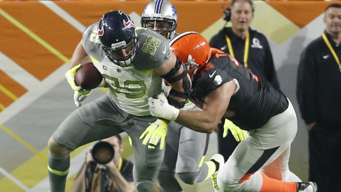 Team Carter DE J.J. Watt from the Texans returns an interception while tackled by Team Irvin tackle Joe Thomas of the Cleveland Browns during the Pro Bowl at University of Phoenix Stadium in Glendale, Ariz., Sunday, Jan. 25, 2015, Ariz