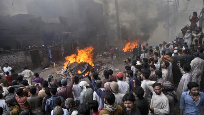 An angry mob gathers after burning Christian houses, in Lahore, Pakistan, Saturday, March 9, 2013. A mob of hundreds of people in the eastern Pakistani city of Lahore attacked a Christian neighborhood Saturday and set fire to homes after hearing accusations that a Christian man had committed blasphemy against Islam's prophet, said a police officer. (AP Photo/K.M. Chaudary)