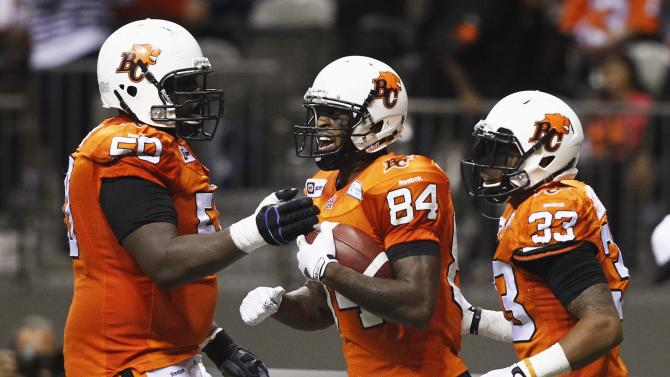 BC Lions' Arceneaux celebrates his touchdown against the Toronto Argonauts with teammates Fabien and Harris during first half CFL game in Vancouver