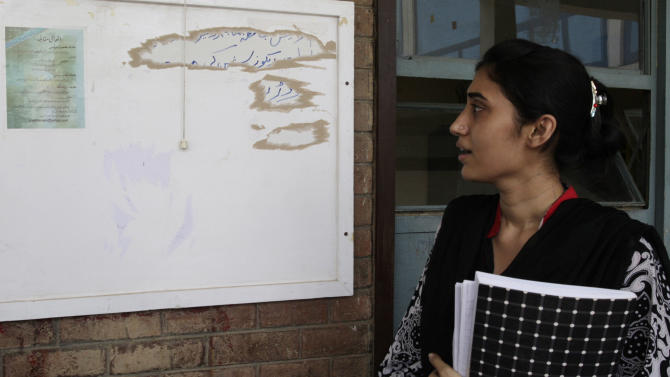 In this June 24, 2011 photo, a Pakistani student looks at a poster advertising a writing contest to glorify the slain al-Qaida chief Osama bin Laden, at the Punjab University in Lahore, Pakistan. Two months after the covert U.S. raid that killed Osama bin Laden, posters emblazoned with images of the burning World Trade Center towers appeared at the prestigious university advertising a literary contest to glorify the slain al-Qaida chief. (AP Photo/K.M. Chaudary)