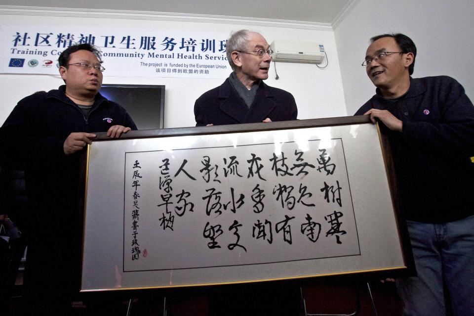 EU President Herman Van Rompuy, center, receives a Chinese calligraphy work as a gift from psychiatric patients during his visit at an EU-funded psychiatric clinic in Beijing Tuesday, Feb. 14, 2012. (AP Photo/Alexander F. Yuan)