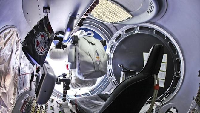 This photo provided by Red Bull Stratos shows pilot Felix Baumgartner, of Austria, preparing to jump from the capsule during the final manned flight for Red Bull Stratos, Sunday, Oct. 14, 2012. In a giant leap from more than 24 miles up, Baumgartner shattered the sound barrier Sunday while making the highest jump ever — a tumbling, death-defying plunge from a balloon to a safe landing in the New Mexico desert. (AP Photo/Red Bull Stratos, Jay Nemeth)