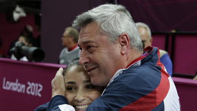U.S. gymnast Alexandra Raisman hugs coach U.S. coach Mihai Brestyan after results were amended and she was declared winner of the bronze medal during the artistic gymnastics women's apparatus finals for the beam at the 2012 Summer Olympics, Tuesday, Aug. 7, 2012, in London. (AP Photo/Gregory Bull)