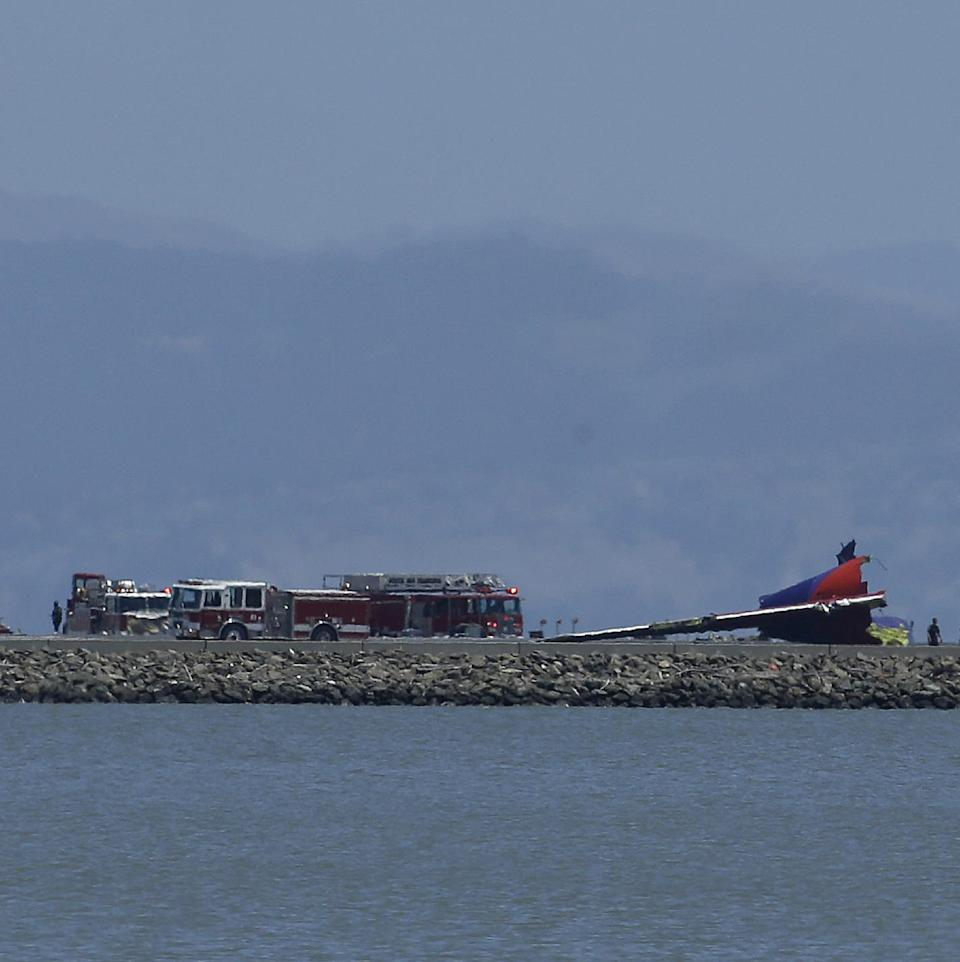 The tail of Asiana Flight 214 is seen, right, after it crashed at San Francisco International Airport in San Francisco, Saturday, July 6, 2013. (AP Photo/Jeff Chiu)