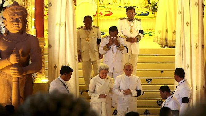 """Cambodian King Norodom Sihamoni, center right, son of the late King Norodom Sihanouk, and his mother, Queen Norodom Monineath, center left, with Cambodia's Prime Minister Hun Sen, covering his mouth, leave the crematorium where the body of the late former Cambodian King Norodom Sihanouk rests in Phnom Penh, Monday, Feb. 4, 2013. Hundreds of thousands of mourners gathered in Cambodia's capital Monday for the cremation of former King Norodom Sihanouk, the revered """"King-Father,"""" who survived wars and the murderous Khmer Rouge regime to hold center stage in the Southeast Asian nation for more than half a century. (AP Photo/Wong Maye-E)"""